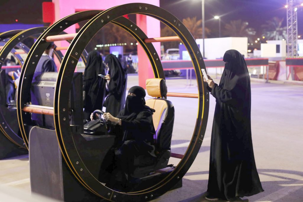 A Saudi woman takes a photo as another woman tries out a car driving simulator in Riyadh, Saudi Arabia. The nation lifted the world's only ban on women driving in June.