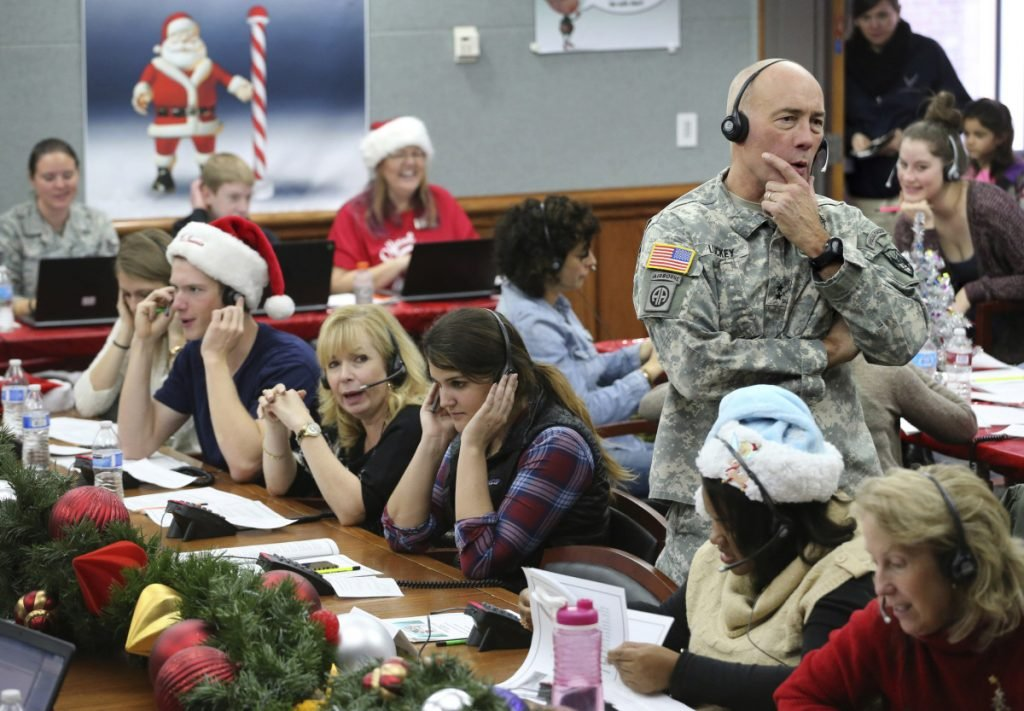NORAD Chief of Staff Maj. Gen. Charles D. Luckey takes a call while volunteering at the NORAD Tracks Santa center at Peterson Air Force Base in Colorado Springs, Colo., in 2014. Hundreds of volunteers will help answer phone calls from children around the world calling for Santa when the program resumes on Monday for the 63rd year.