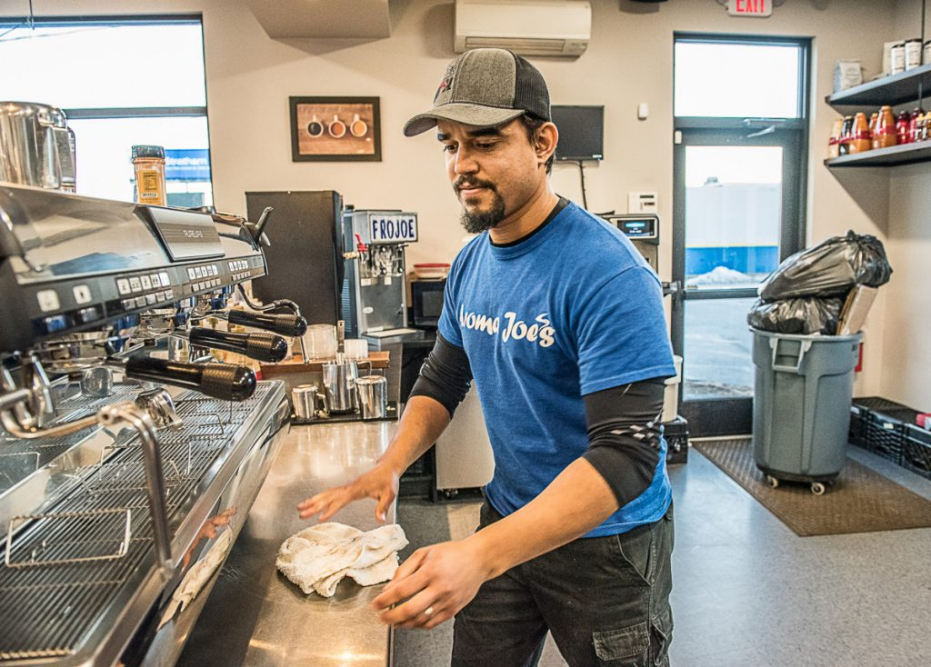 Tulio DeAlmeida cleans up after a busy day at Aroma Joe's in Auburn. He and his family worked so their employees could take Christmas Day off.