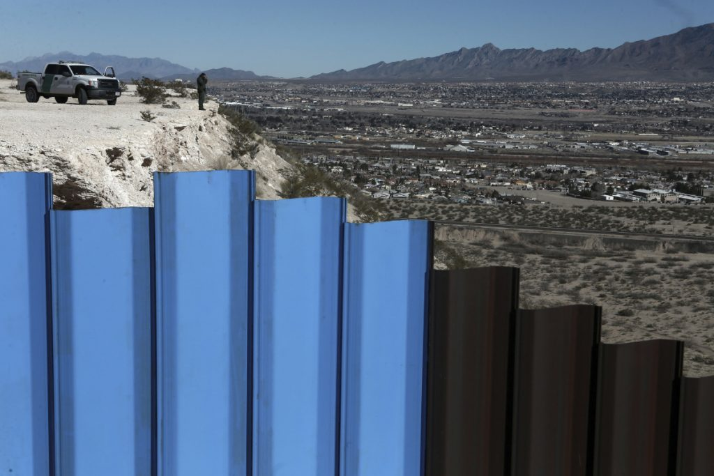 An agent from the border patrol observes near the Mexico-U.S. border fence separating Anapra, Mexico, and Sunland Park, N.M. An 8-year-old boy from Guatemala died in government custody early Christmas Day.