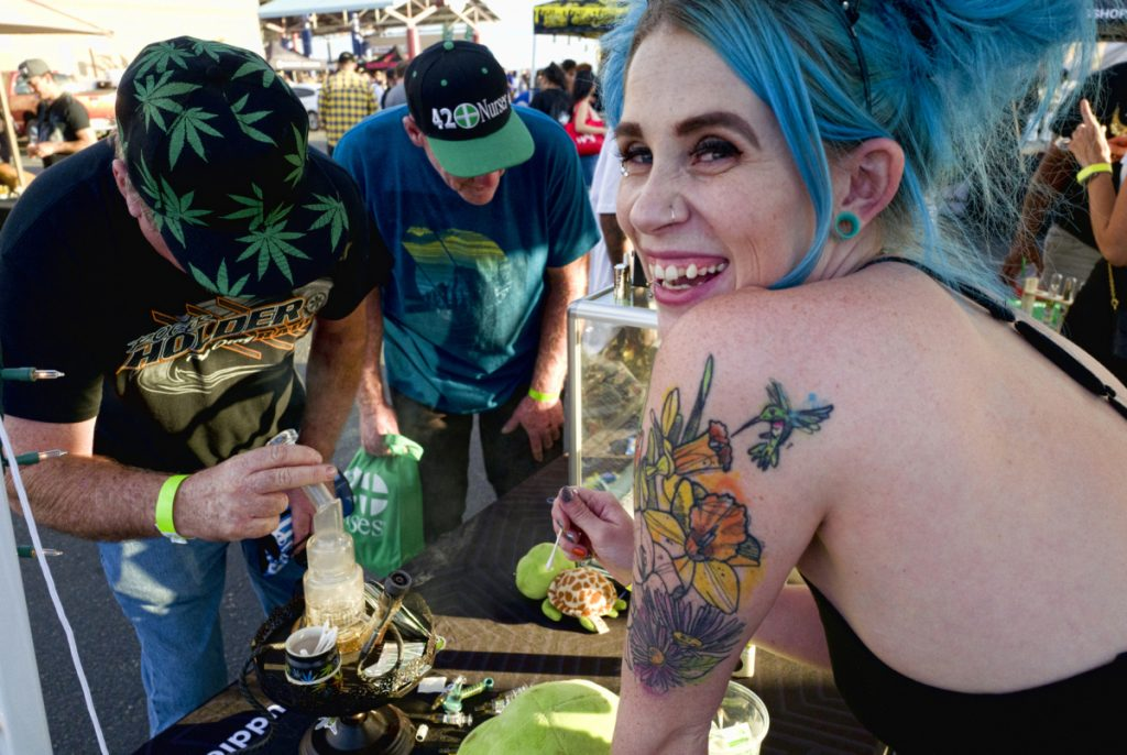 Bud tender Kansas, right, offers customers a puff of cannabis concentrate at the Turtle Puddles' booth at a festival in Adelanto, Calif., in October. Legalization is spreading around the world.
