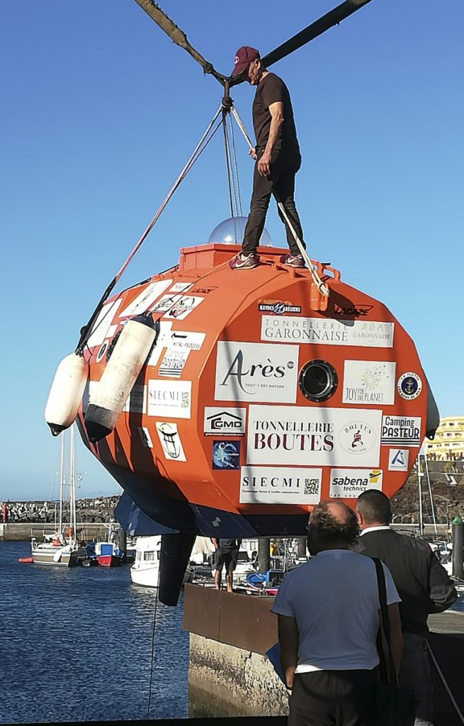 In photograph taken Saturday, 71-year-old Frenchman Jean-Jacques Savin stands on top of his 10-foot-long, 7-foot-wide resin-coated plywood capsule, which will use ocean currents alone to propel him across the sea. Savin set off from El Hierro in Spain's Canary Islands.