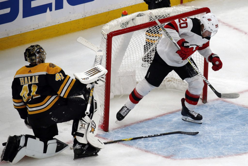 New Jersey Devils center Blake Coleman comes out of the net after scoring a breakaway goal against Boston Bruins goaltender Jaroslav Halak during the Devils' 5-2 win Thursday in Boston.