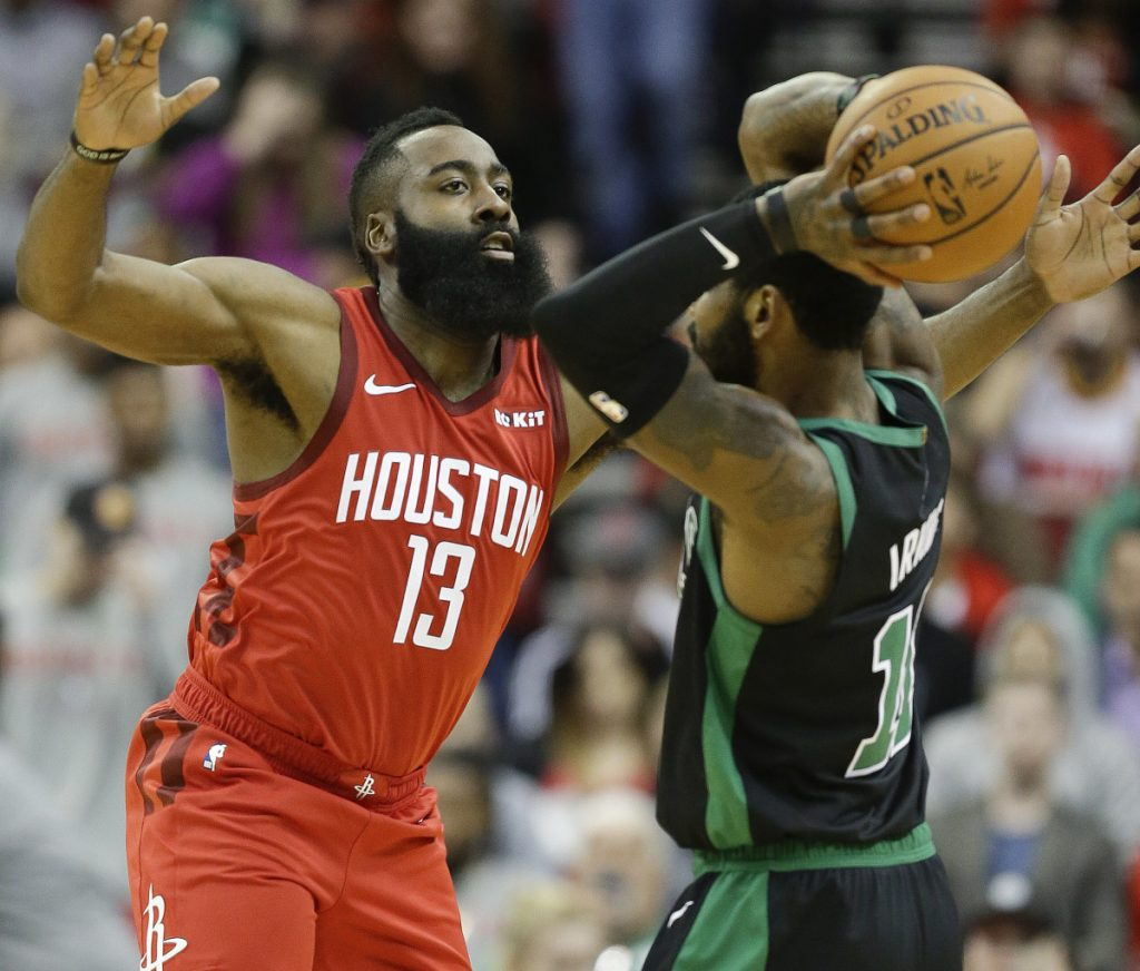 Houston Rockets guard James Harden applies defensive pressure against Boston Celtics guard Kyrie Irving during the first half of the Rockets' 127-113 win Thursday in Houston.
