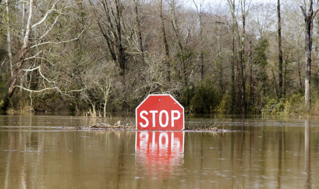 A stop sign is partially submerged in water from the flooded Okatibbee River in Meridian, Miss., on Friday. Flash flood watches and warnings were posted for much of the South from Louisiana to Virginia.