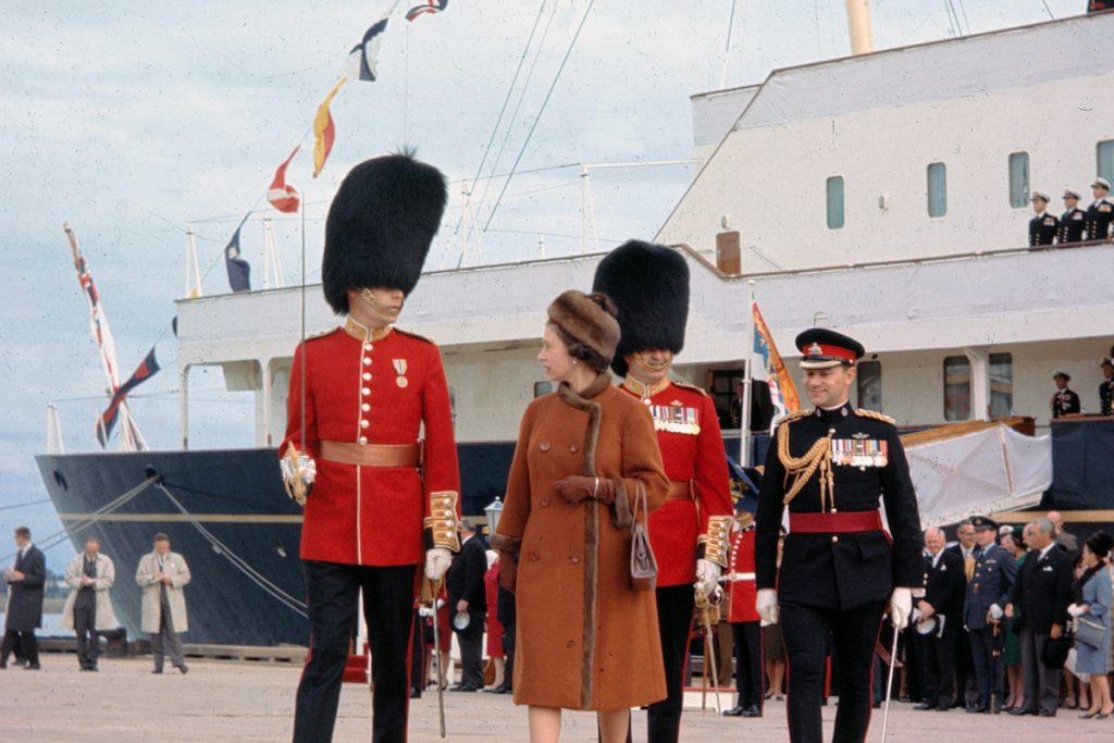 Queen Elizabeth II is escorted by Capt. G.L. Simpson as she leaves the Royal Yacht Britannia in 1964 in Charlottetown, Canada. The Royal Yacht Britannia was in service from 1954 to 1997.