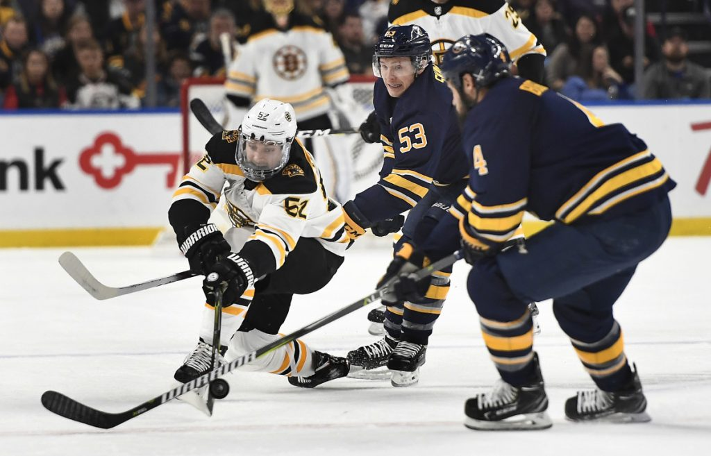 Boston center Sean Kuraly, left, reaches for a puck against Buffalo's Zach Bogosian, right, and Jeff Skinner during Saturday's game in Buffalo, N.Y. Kuraly scored in overtime to give Boston a 3-2 win.