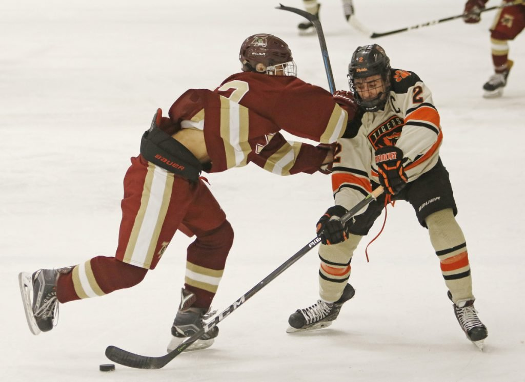 Richard Martin of Thornton Academy, left, attempts to knock Colin Petit of Biddeford off the puck during the second period of Biddeford's 5-4 victory Monday at the Biddeford Ice Arena.