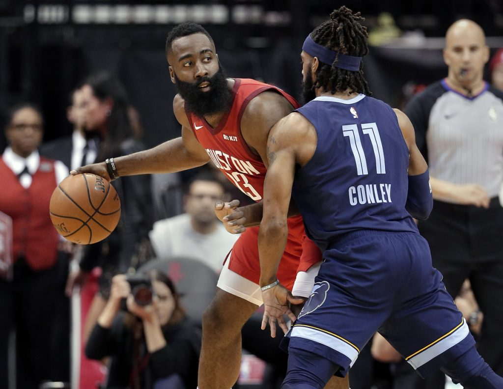 Houston guard James Harden looks to pass the ball under pressure from Memphis guard Mike Conley during the first half Monday in Houston.
