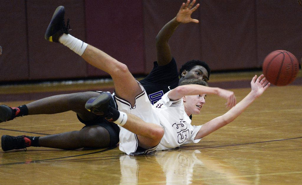 Gorham's Nick Strout makes a pass from the floor after coming up with a loose ball as Deering's Mpore Semuhoza plays defense during Deering's 61-58 win Monday in Gorham.