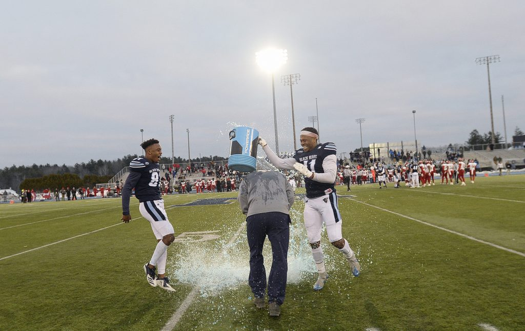 UMaine's Earnest Edwards, left, and Jaquan Blair dump a bucket of icy refreshment over the head of Coach Joe Harasymiak after the clock winds down on the Black Bears' 55-27 win over Jacksonville State in the second round of the FCS playoffs on Saturday in Orono.