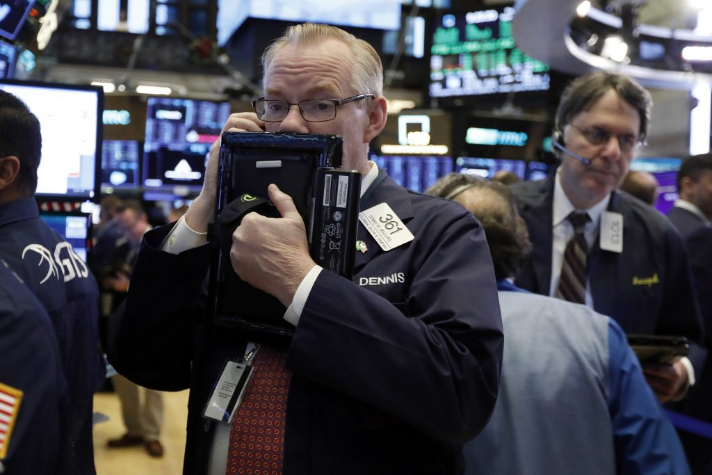 In this Thursday, Nov. 29, 2018, file photo trader Dennis Maguire, left, works on the floor of the New York Stock Exchange.