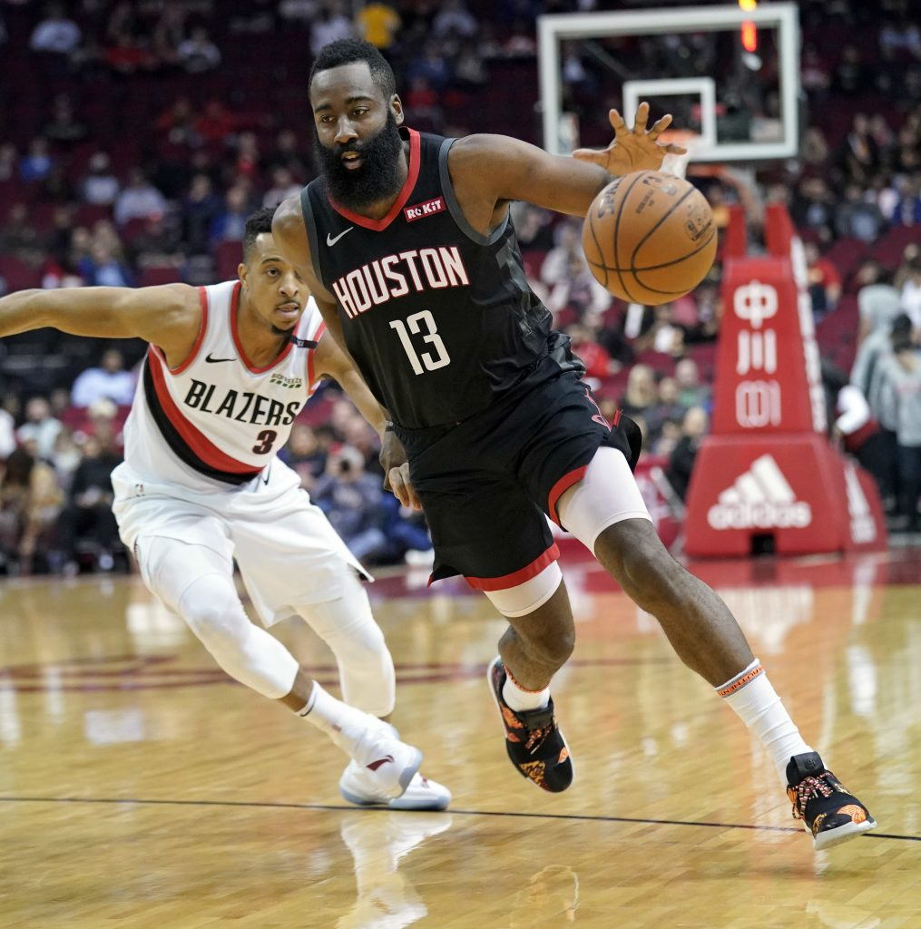 Houston Rockets' James Harden drives past Portland Trail Blazers' CJ McCollum during the Rockets' 111-104 win on Tuesday in Houston.