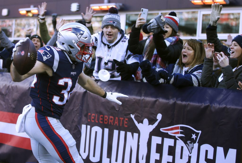 New England Patriots running back Rex Burkhead celebrates his touchdown with fans in the end zone stands during the first half of the Patriots' 38-3 win over the Jets that gave the Patriots a first-round bye.