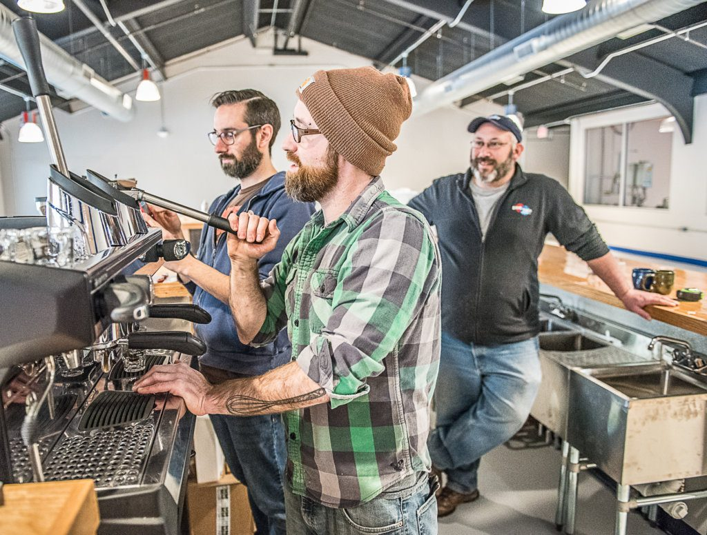 Nathan Hahn, left, of Coffee By Design walks Willis Croninger through the process of pulling the first press of espresso at Side By Each Brewing Co. in Auburn, as owner Ben Low looks on, right. The business will open in January with coffee and beer sampling.