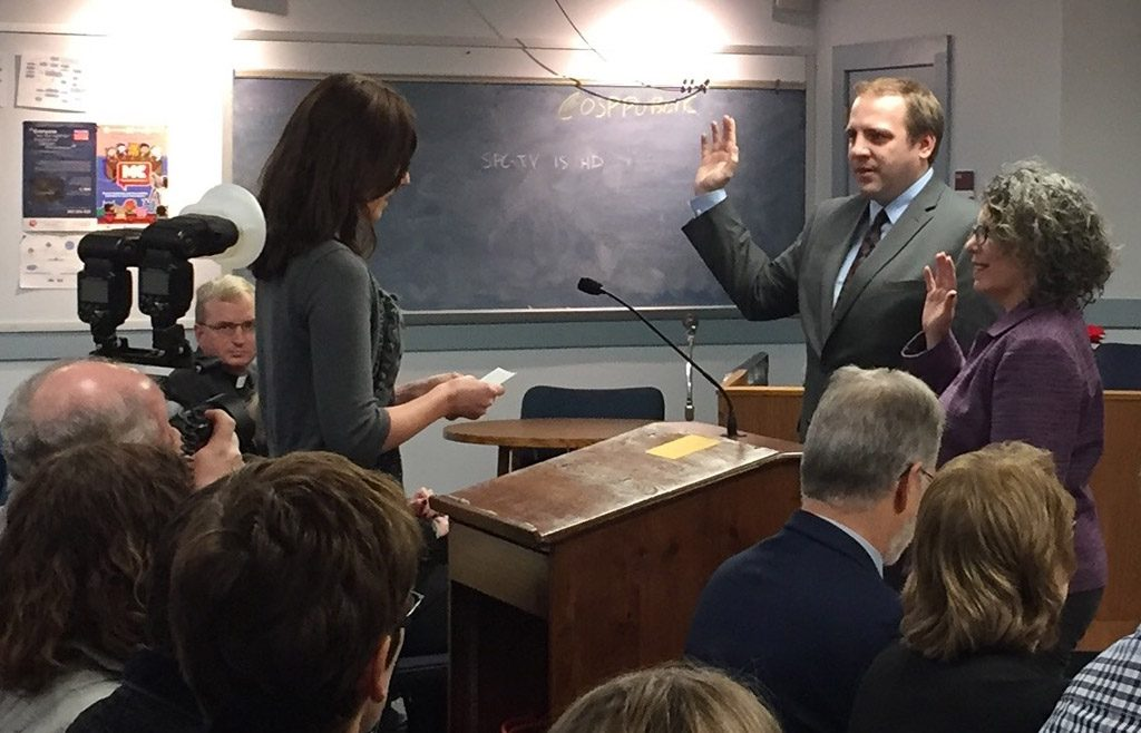 New South Portland City Councilors Misha Pride and April Caricchio are sworn in by City Clerk Emily Scully on Monday.
