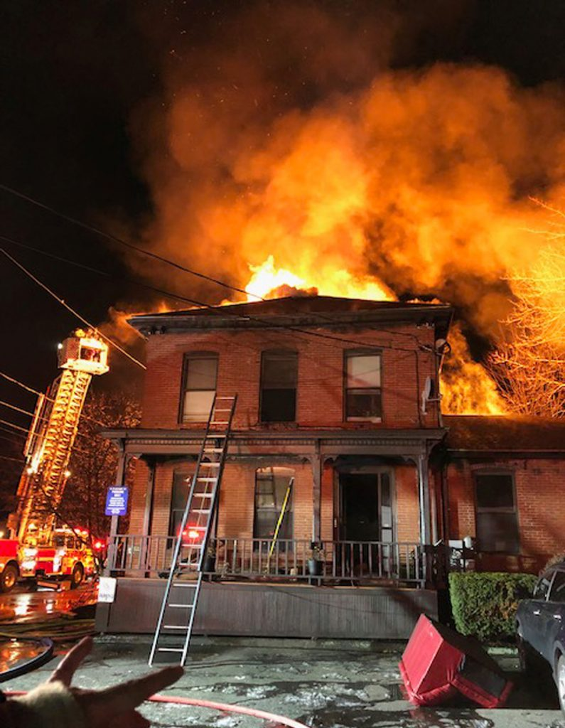 Fire shows through the roof of a building at 13 Pleasant Street in Westbrook on Sunday, December 30. The building housed a dentist's office and had an apartment on the top floor that housed five people.