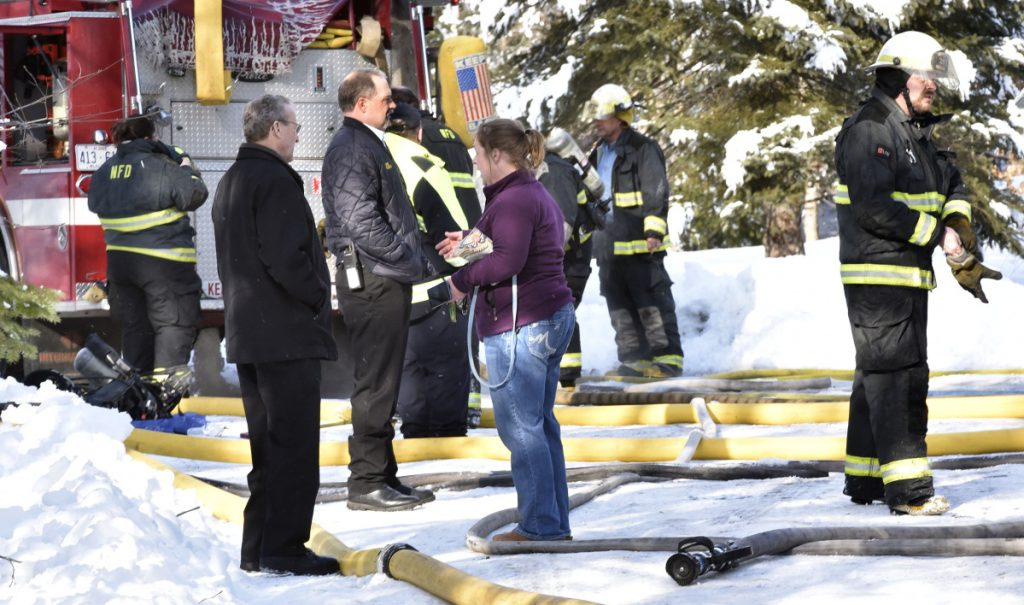 Homeowner Tracy Moody speaks with friend Larry Jones, left, and Skowhegan Fire Chief Shawn Howard as firefighters extinguish the fire that destroyed her mobile home in Norridgewock on Wednesday.