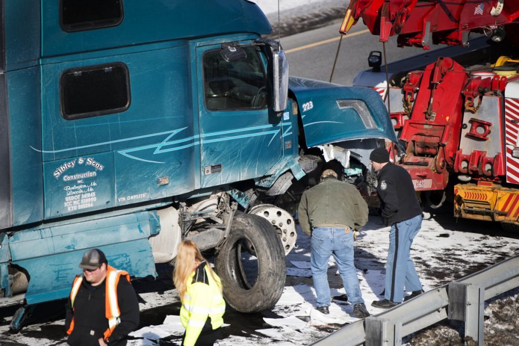 A Maine State Police trooper inspects the damage to a tractor-trailer that struck an Interstate 95 guardrail Saturday on the northbound side of exit 120 in Sidney.