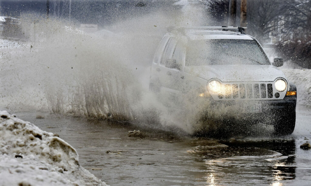 A vehicle blasts water from a huge puddle that developed on Oak Street in Waterville as rain and warm weather combined to make Thursday wet and messy.