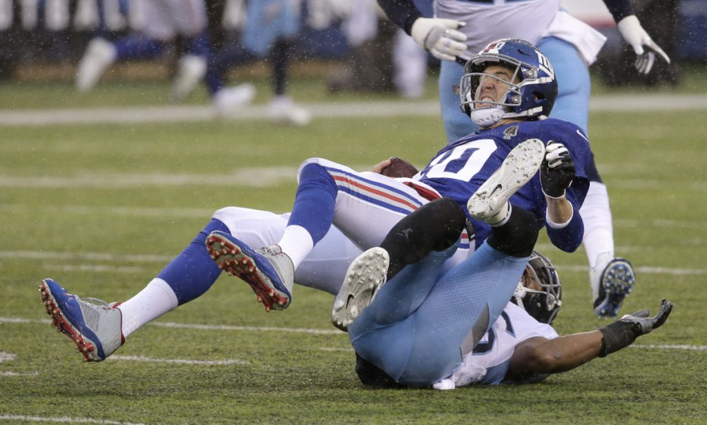 New York Giants quarterback Eli Manning, top, was battered and bruised this season, and on Wednesday did not get a vote of confidence from General Manager Dave Gettleman, who would not say if the team will bring back Manning for a 16th season.