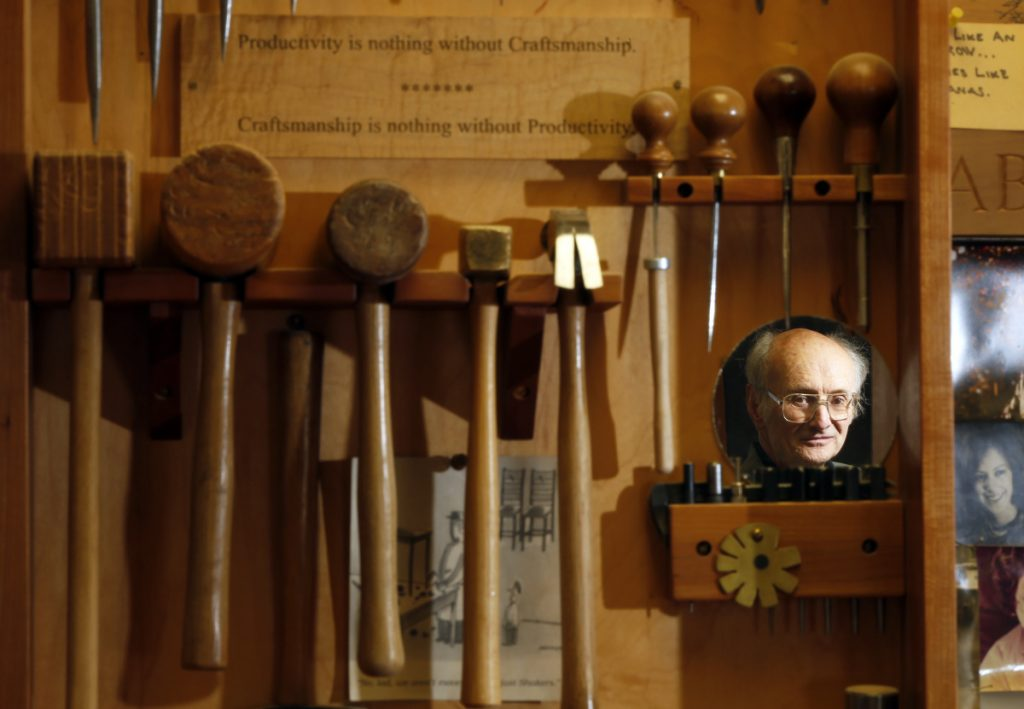 """Master woodworker Christian Becksvoort is reflected in a mirror on the tool chest in his New Gloucester shop, where a sign reads """"Productivity is nothing without Craftsmanship ... Craftsmanship is nothing without Productivity."""""""