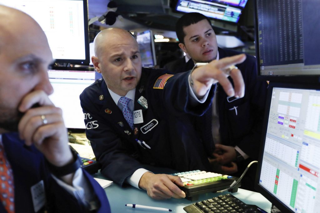 Mario Picone, center, works with fellow specialists on the floor of the New York Stock Exchange on Friday. Investors welcomed news of trade talks between the U.S. and China and a big gain in jobs in the U.S.