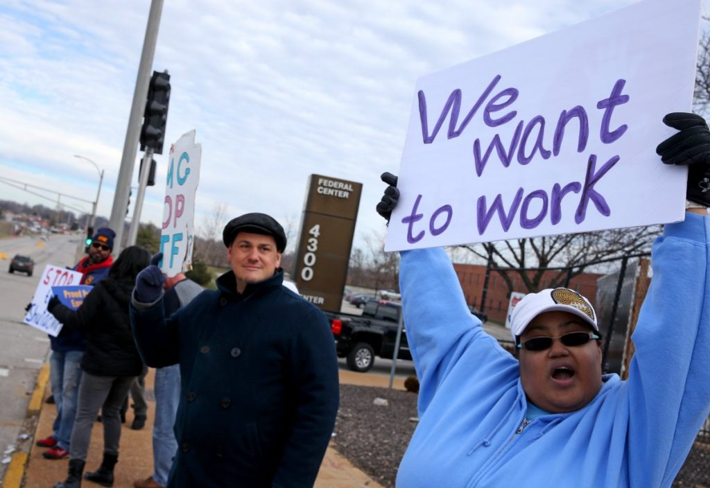 Emma James, right, and co-worker Vincent Cuenca protest the government shutdown outside the Federal Center on Friday in St. Louis. James is a processor in the multifamily housing division. Cuenta processes payments to FEMA contractors.