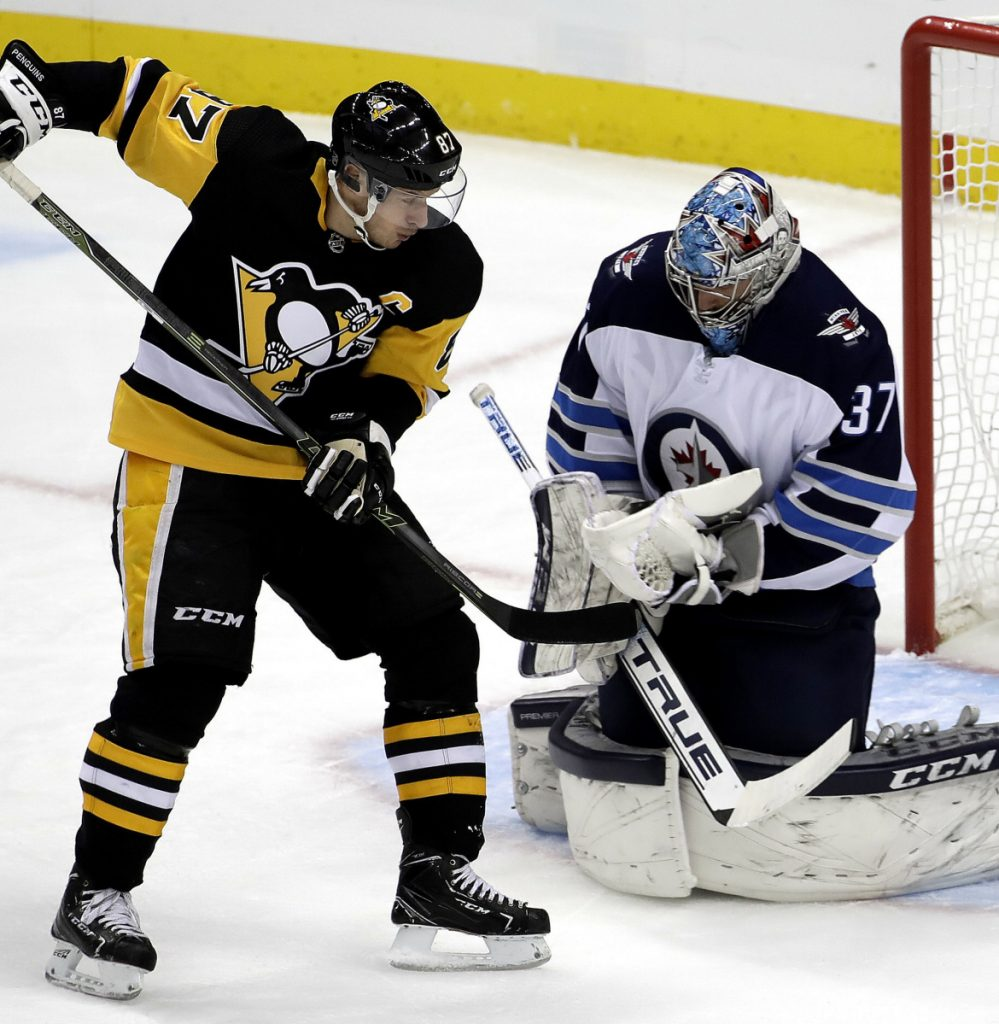 Winnipeg goalie Connor Hellebuyck makes a save while Sidney Crosby of the Penguins looks for the rebound Friday during Pittsburgh's 4-0 win.