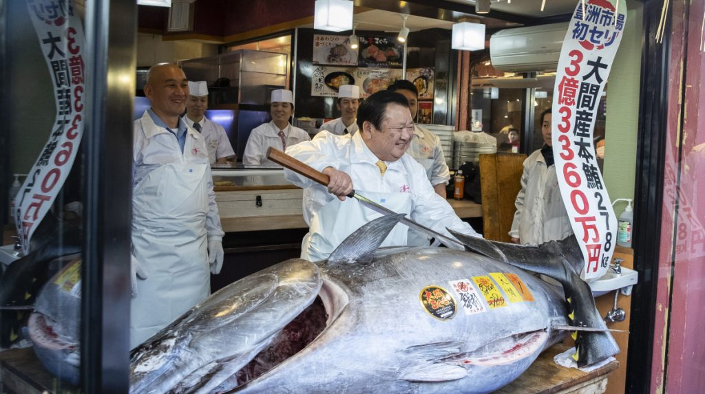 Kiyoshi Kimura, president of Kiyomura Corp., poses with a newly purchased bluefin tuna at a Sushizanmai restaurant in Tokyo on Saturday. The record price was more than double the previous high set for a bluefin in 2013.