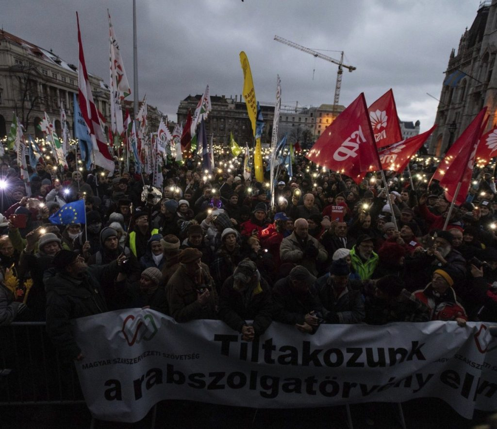 "Anti-government demonstrators carry a banner reading ""We protest against the slave bill"" as they protest in front of the Parliament building at Kossuth Square in Budapest, Hungary, on Saturday."