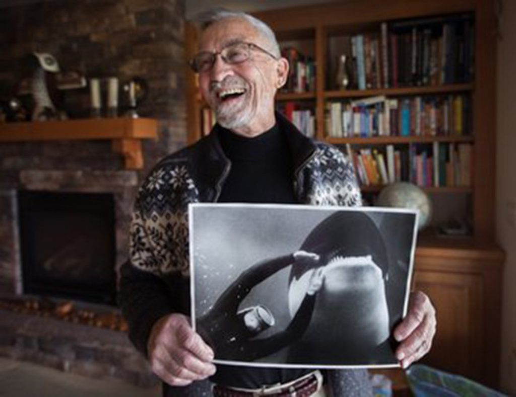 Ted Griffin, the first to capture and befriend an orca in Puget Sound in 1965, holds a photo by National Geographic of him with Namu. His actions set off a craze for killer whales that would imperil the species.