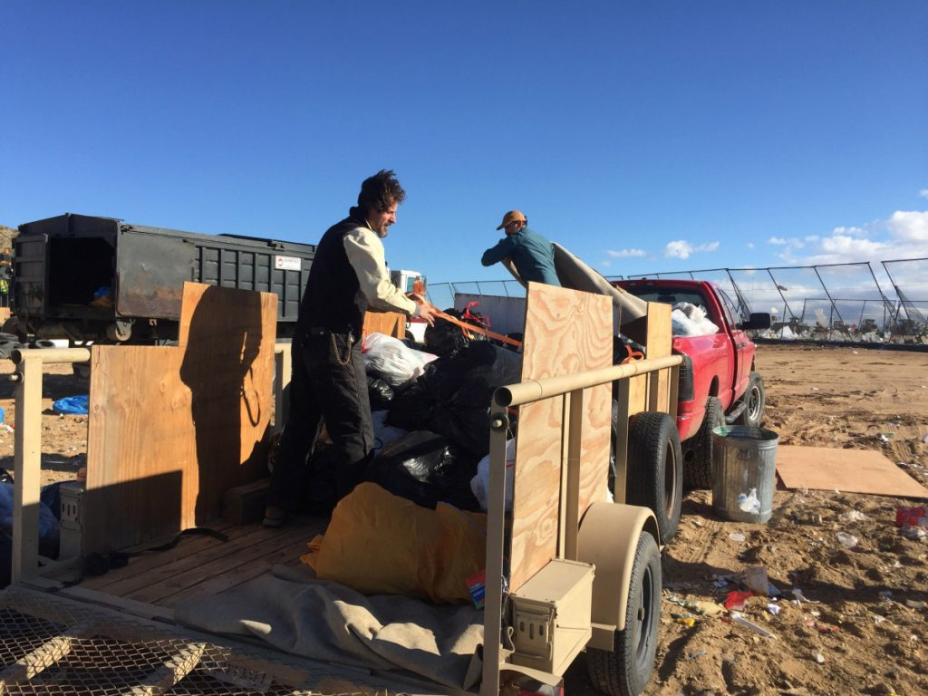 Volunteers Travis Puglisi and Shawn Snyder load a trailer of trash in Joshua Tree National Park on Dec. 31.