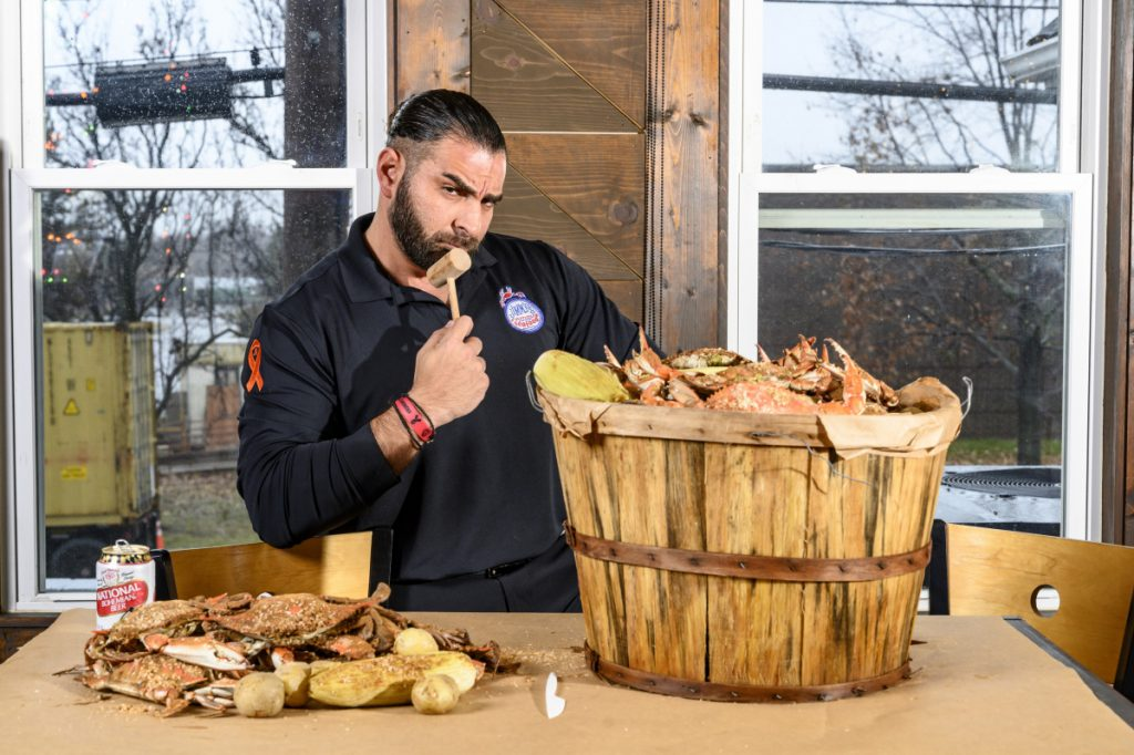 John Minadakis, owner of Jimmy's Famous Seafood, with a bushel of steamed crabs. PETA targeted Baltimore, putting up a billboard against eating seafood. He responded with his own billboard.