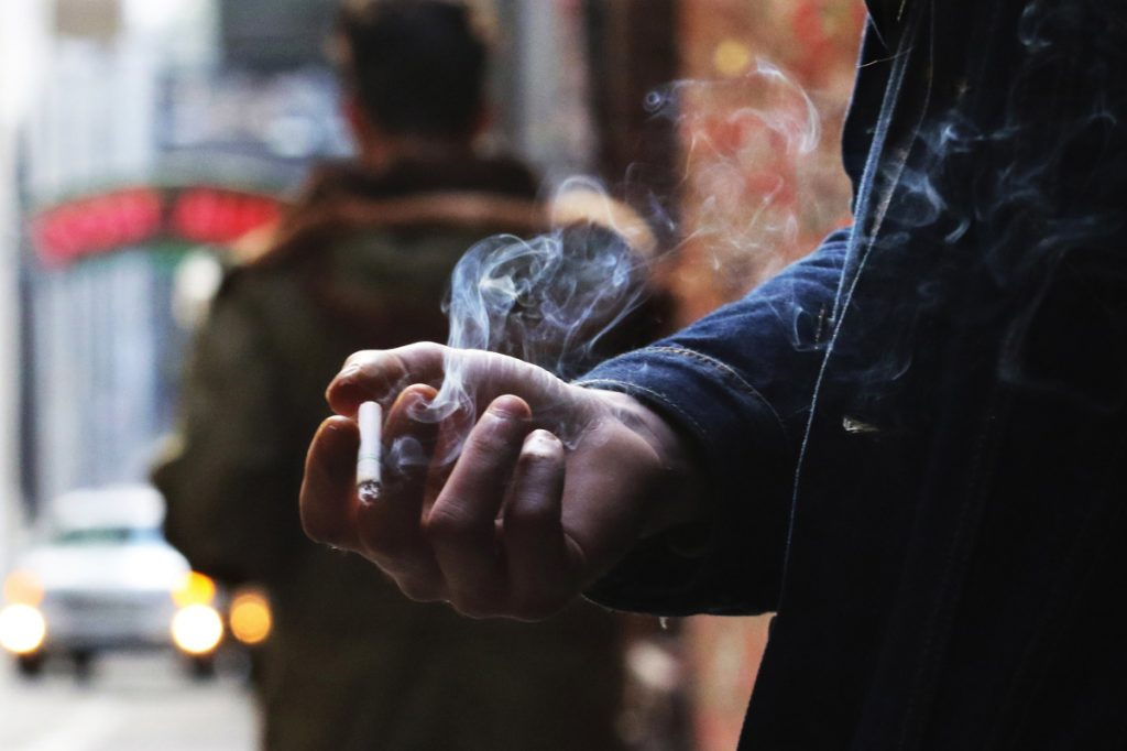 "Leyland Foster has a cigarette break in Post Alley, smoking a Camel Crush with a capsule in the filter that, when squeezed, releases menthol flavor. He's been smoking since he was 16, about 14 years. ""With coffee, oh yeah."" (Alan Berner/Seattle Times/TNS)"