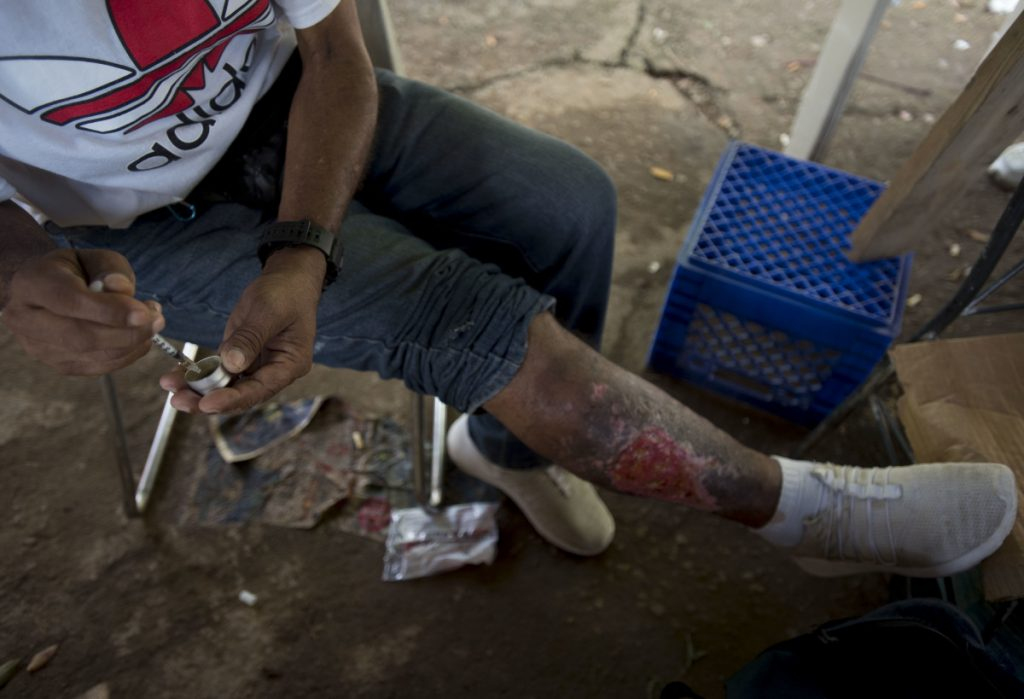 A man fills his syringe with heroin in an area popular with users behind an abandoned home in Humacao, Puerto Rico. The user, who did not want to give his name, said an infection on his leg developed as a result of repeatedly injecting cocaine. He said he uses cocaine to balance out the effect of heroin.