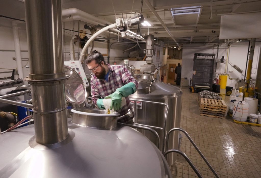 Brewer Mike O'Neal adds hops to a batch of Daymark on Tuesday at Rising Tide Brewing Co. in Portland. The partial government shutdown could cause some breweries to delay release of any new brew batches.
