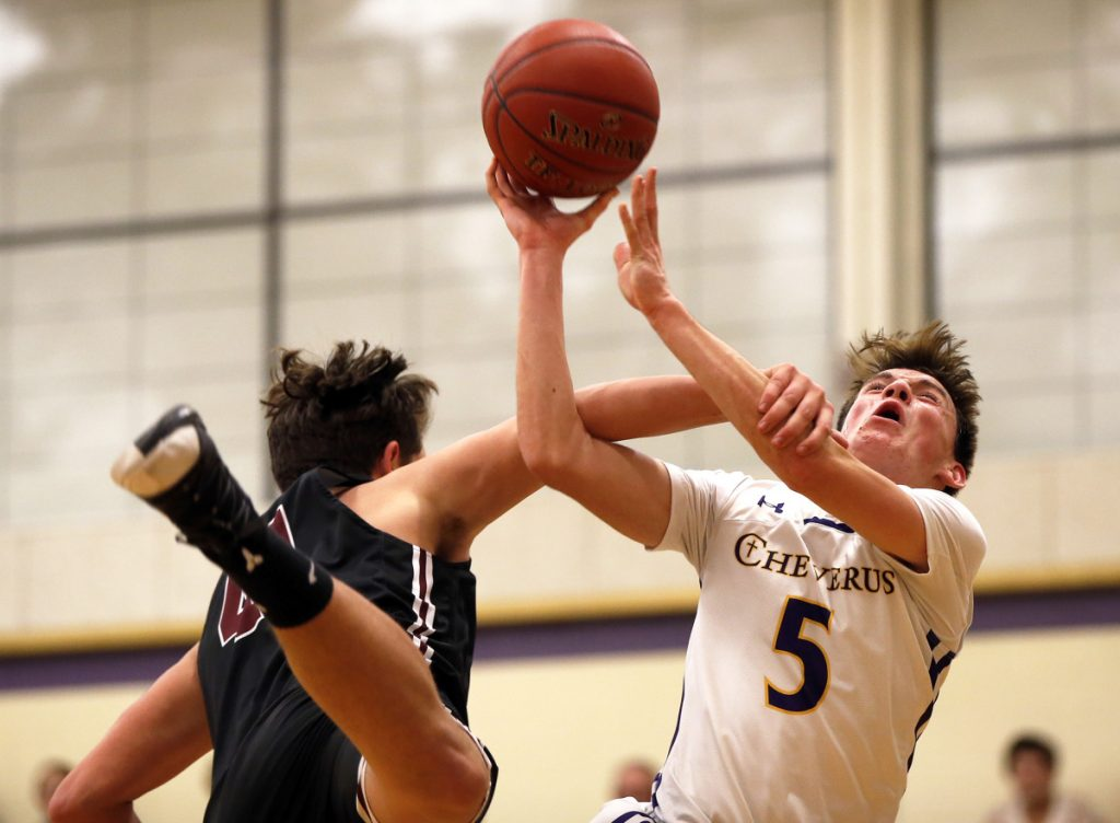Owen Burke of Cheverus reacts as Henry O'Neill of Gorham goes for a block during Tuesday night's game in Portland. The Stags improved to 6-4 with a 68-64 win.