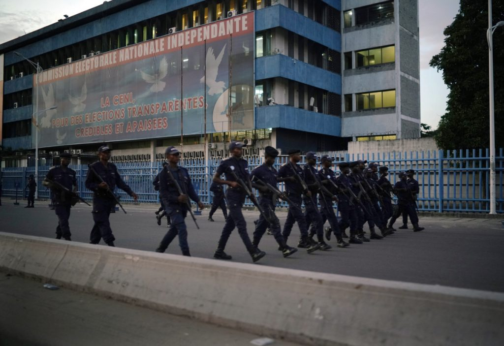 Congolese riot police patrol Thursday outside the independent electoral commission building at dusk in Kinshasa. Few election protests were reported.
