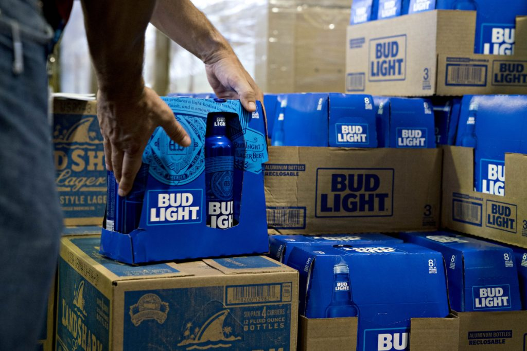 An employee adjusts bottles of Bud Light brand beer at an Anheuser-Busch InBev NV facility in Williamsburg, Va. Bud Light will begin including standard white nutrition labels on case boxes and six-packs next month.