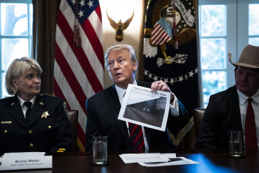 "President Trump holds up a photo of a ""typical standard wall design"" as he speaks during a roundtable discussion on border security with administration officials at the White House on Friday."