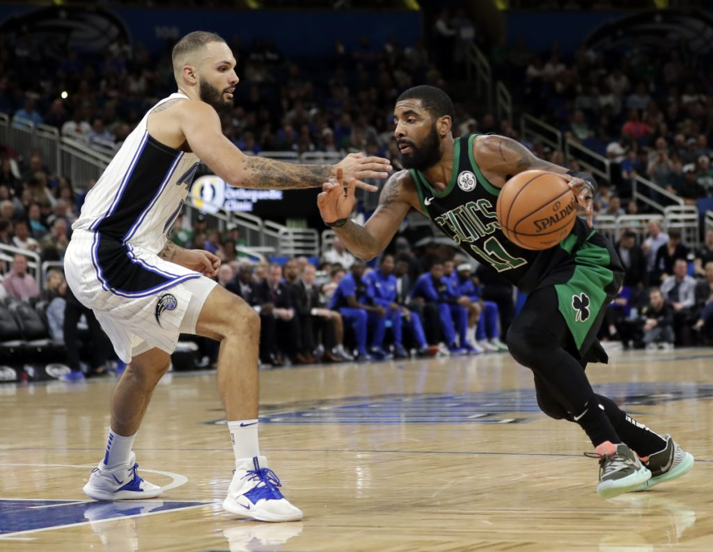 Kyrie Irving of the Celtics drives around Orlando's Evan Fournier during Boston's 105-103 loss Saturday night.