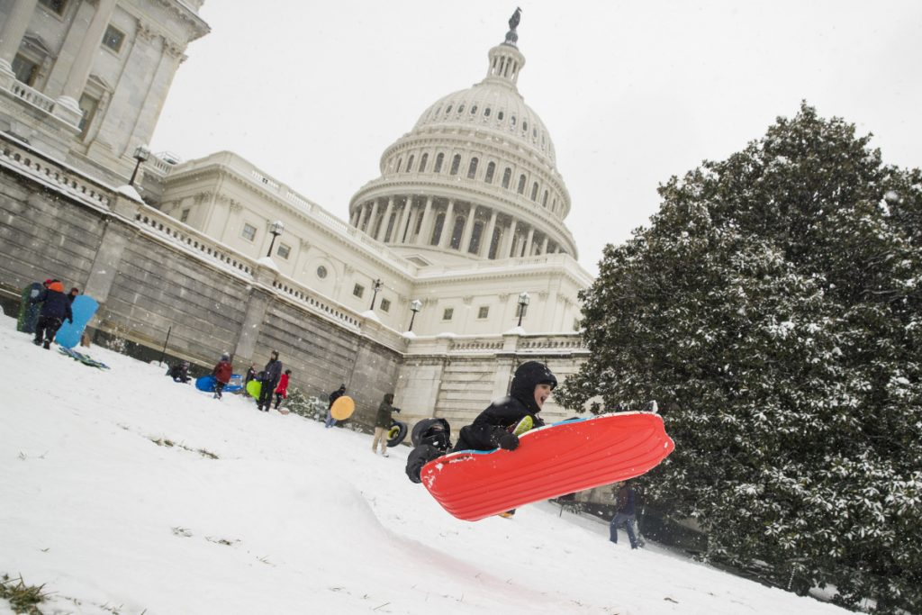 Two children go over a ramp as they sled on Capitol Hill as a winter storm arrives in the region, Sunday in Washington. Associated Press /Alex Brandon