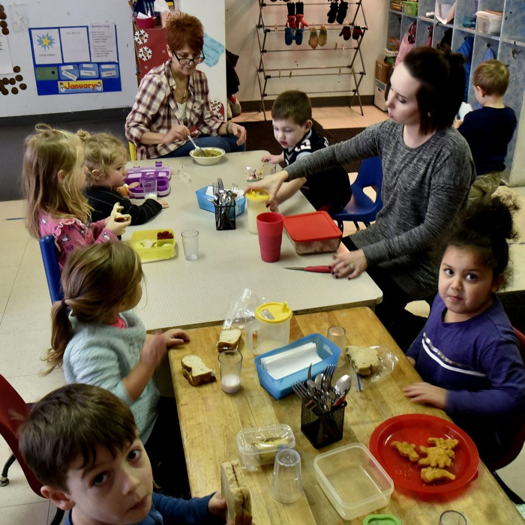 Teachers and children sit together for lunch in the pre-school room at the Children's Place at the Maine Children's Home for Little Wanderers in Waterville.