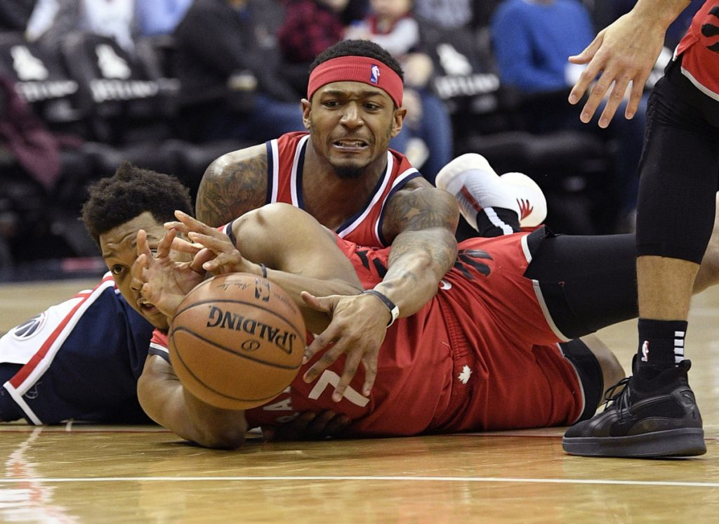 Bradley Beal of the Washington Wizards, top, competes for the ball with Kyle Lowry of the Toronto Raptors during the second half of Toronto's double-overtime win Sunday.