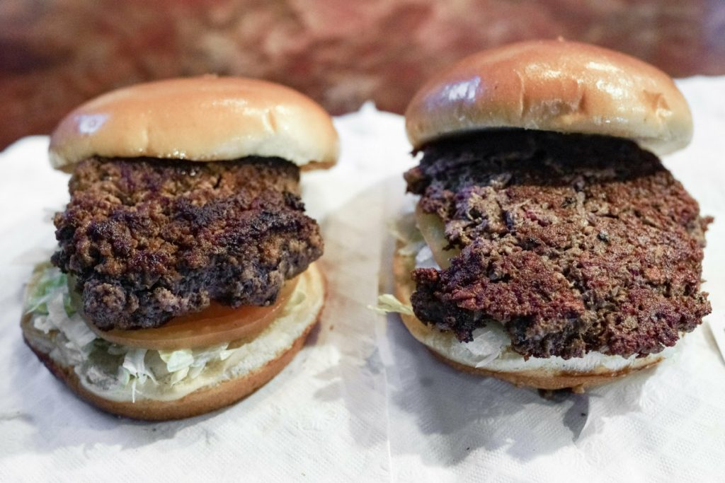"""A conventional beef burger, left, is seen next to """"The Impossible Burger"""", a plant-based burger containing wheat protein, coconut oil and potato protein among it's ingredients. The ingredients of the Impossible Burger are clearly printed on the menu at Stella's Bar & Grill in Bellevue, Neb., where the meat and non-meat burgers are served. More than four months after Missouri became the first U.S. state to regulate the term """"meat"""" on product labels, Nebraska's powerful farm groups are pushing for similar protection from veggie burgers, tofu dogs and other items that look and taste like meat."""