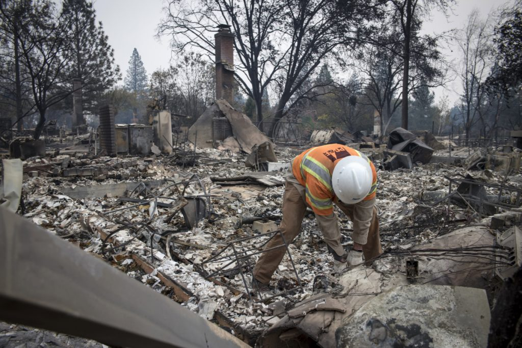 A Pacific Gas and Electric Co. worker locates a gas main line in front of a home during the Camp Fire in Paradise, Calif., in November.