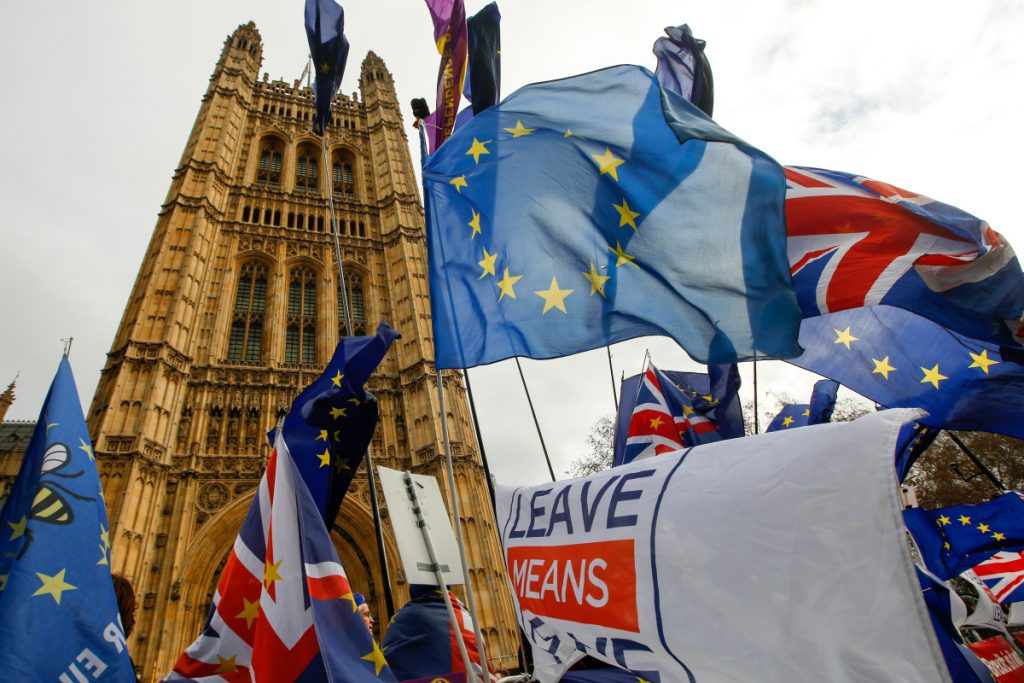 Anti and pro-Brexit demonstrators wave European Union flags, Union Jacks and banners during protests outside the Houses of Parliament in London on Tuesday, when British lawmakers were voting on a plan to exit the European Union.