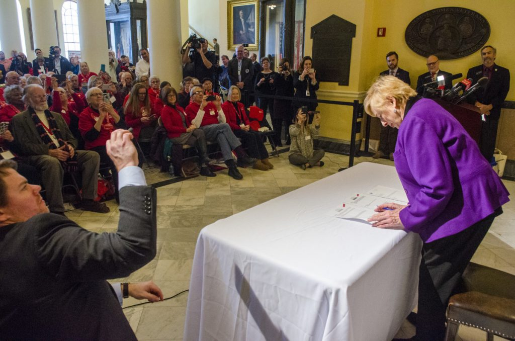 Spectators, many wearing red AARP shirts, watch as Gov. Janet Mills signs bonds for affordable senior housing on Tuesday in the Maine State House Hall of Flags in Augusta. Mills' predecessor, Republican Gov. Paul LePage, had refused to release the bonds for more than three years.