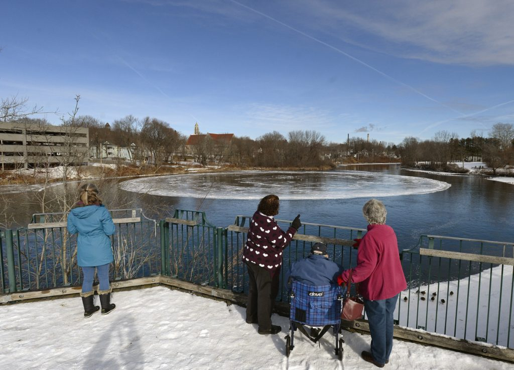 Curious observers watch the rotating disk of ice Tuesday on the Presumpscot River in Westbrook. One theory of how it formed: The flow of the river is pushing the ice disk along like a paddle wheel as ice builds up on the edges.